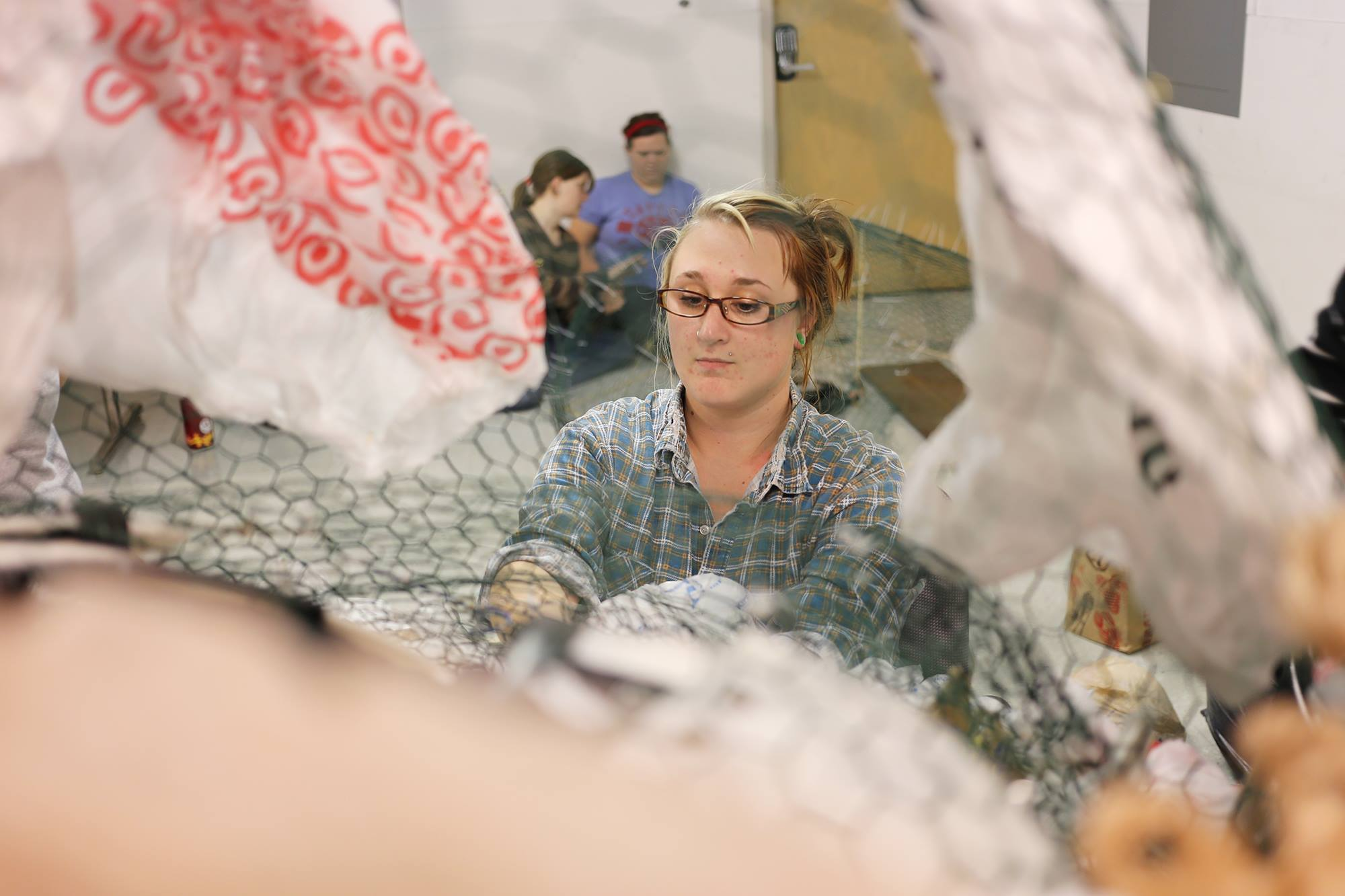 AmeriCorps member, Nicole, working with chicken wire to build an enviro-character for Earthfest