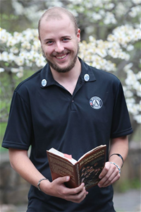 AmeriCorps member, Joseph, holding a book while standing in front of blooming dogwoods