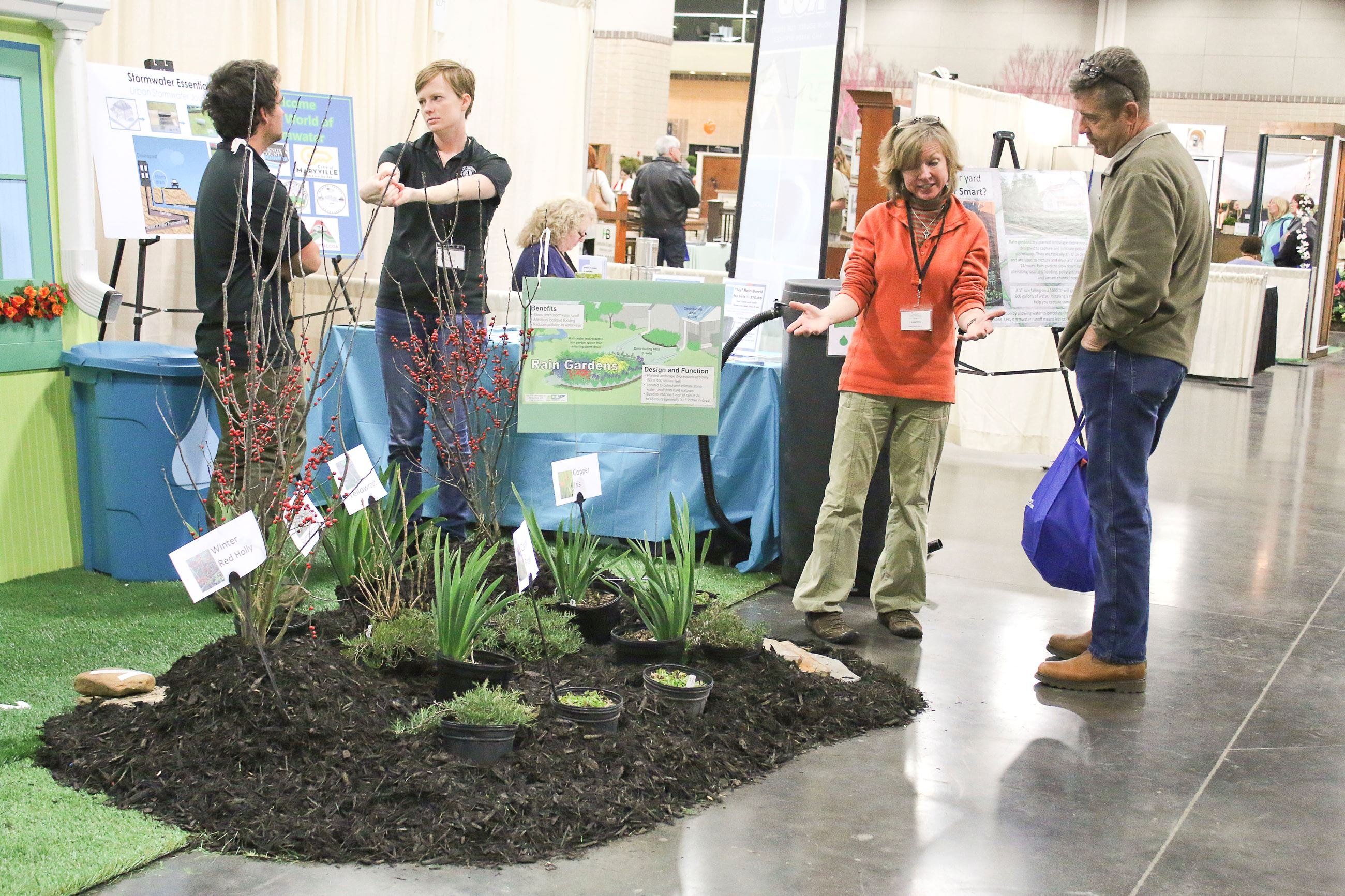 Woman speaking to event attendee about the rain garden display