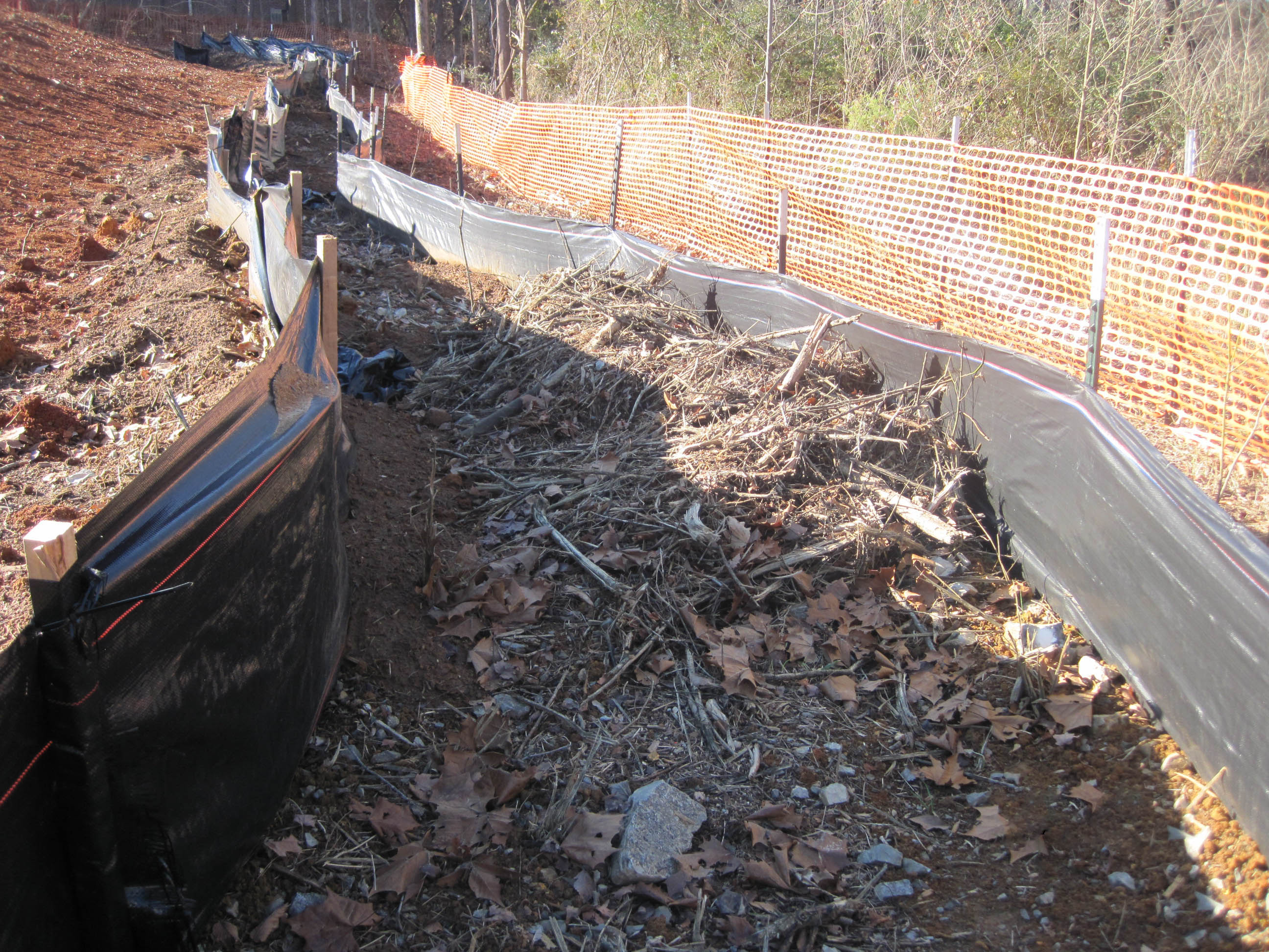 Double row of silt fence on a construction site with a mulch berm in between