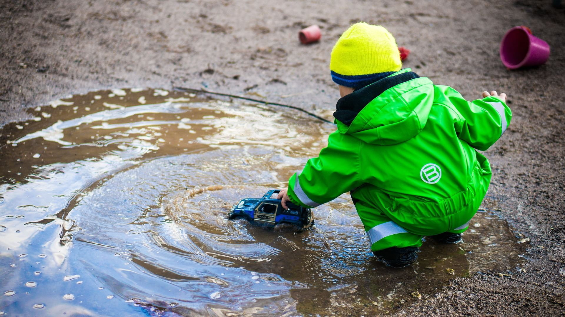 young boy wearing a rain suit and playing with a blue truck in a large puddle
