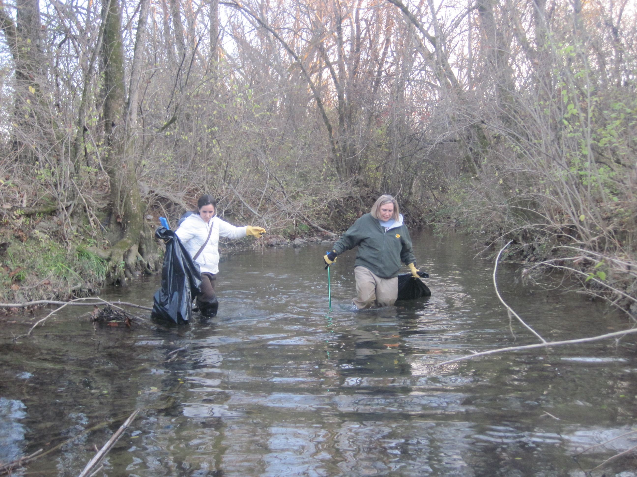 two ladies in a stream collecting trash with trash pickers