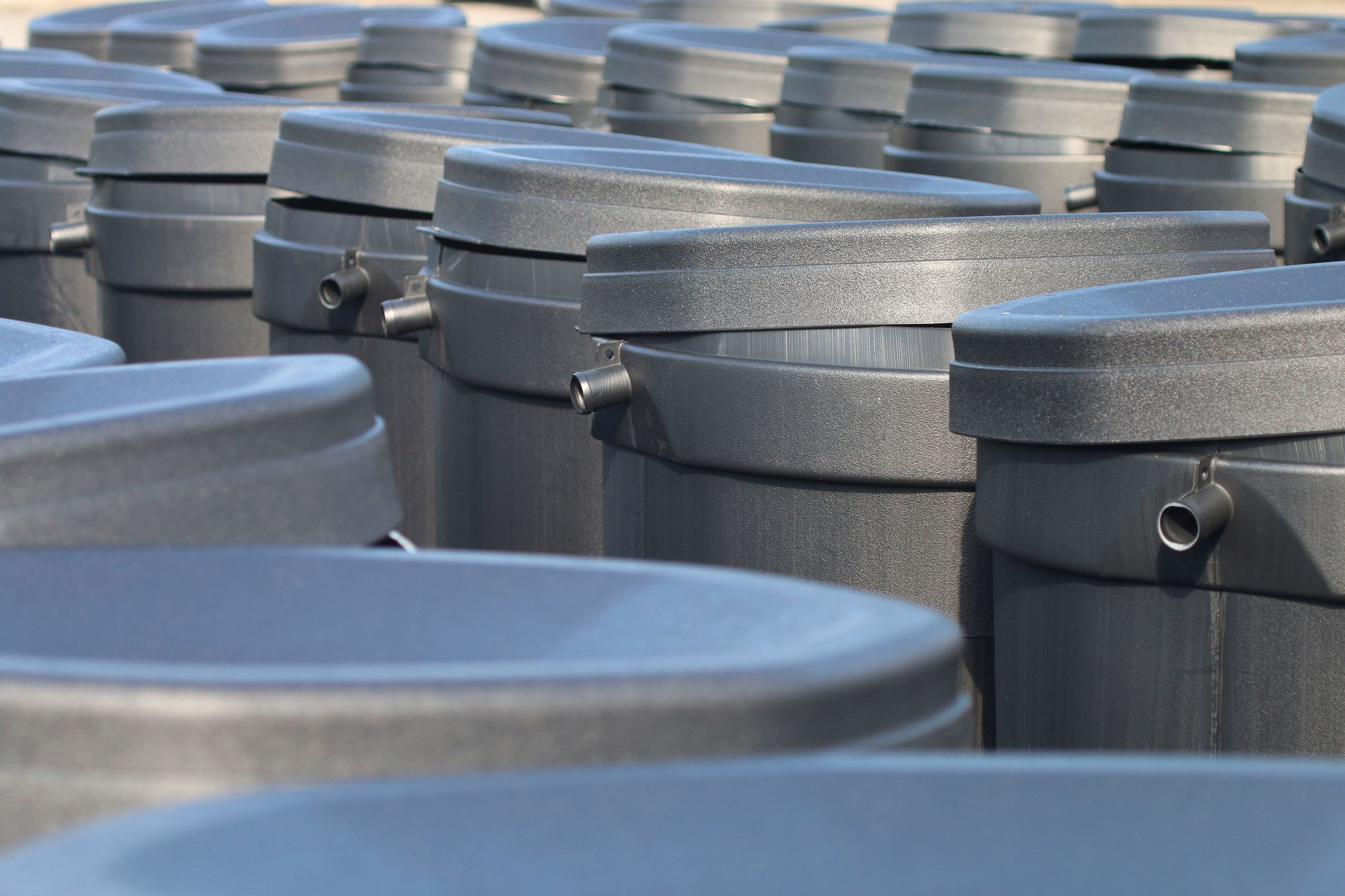 close up of many grey rain barrels lined up together