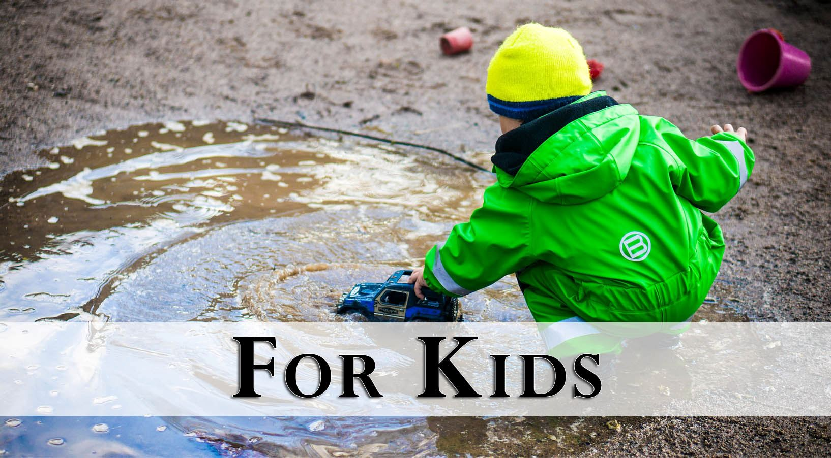 boy playing in the mud with toy truck
