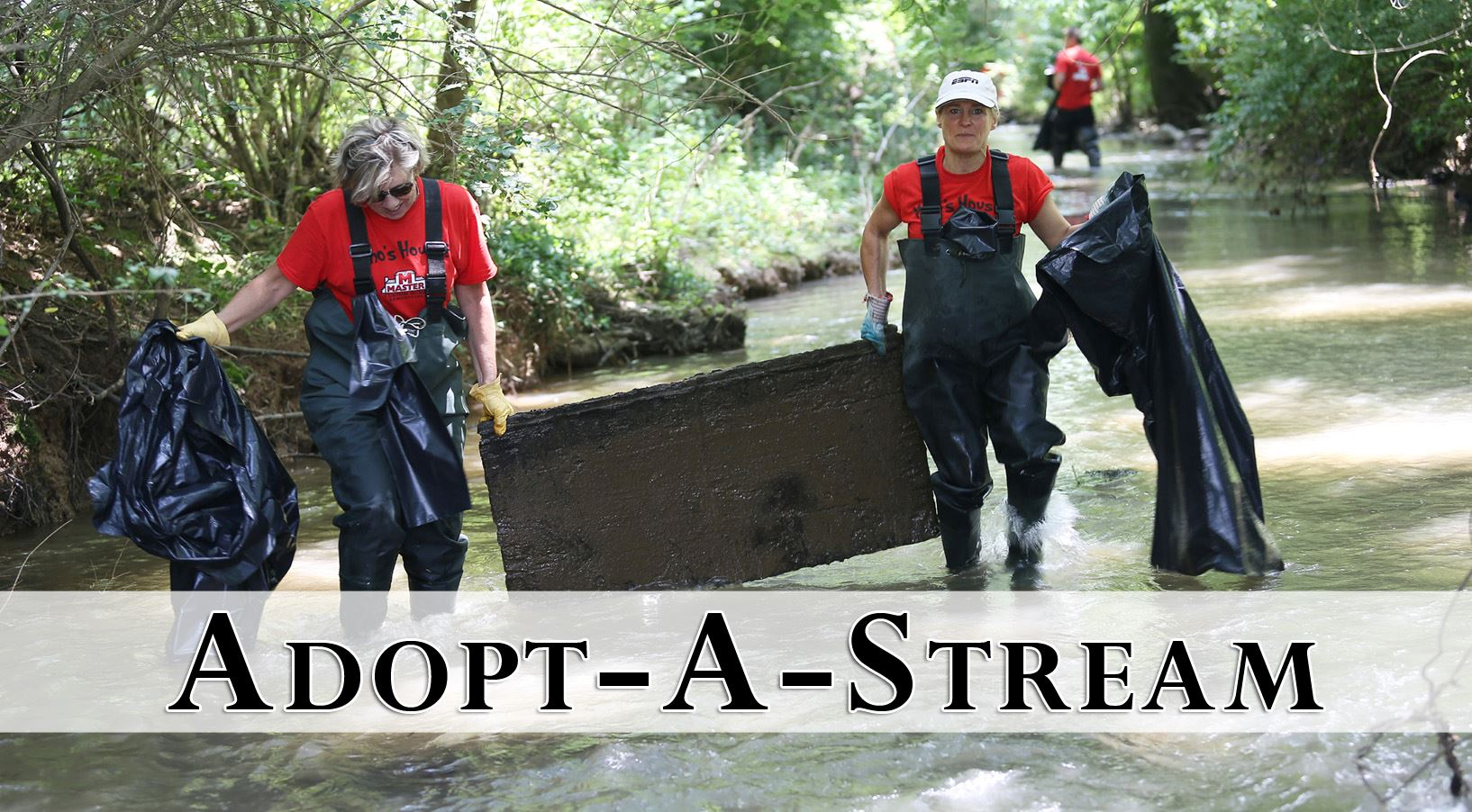 adult volunteers in a stream wearing waders and carrying a large board