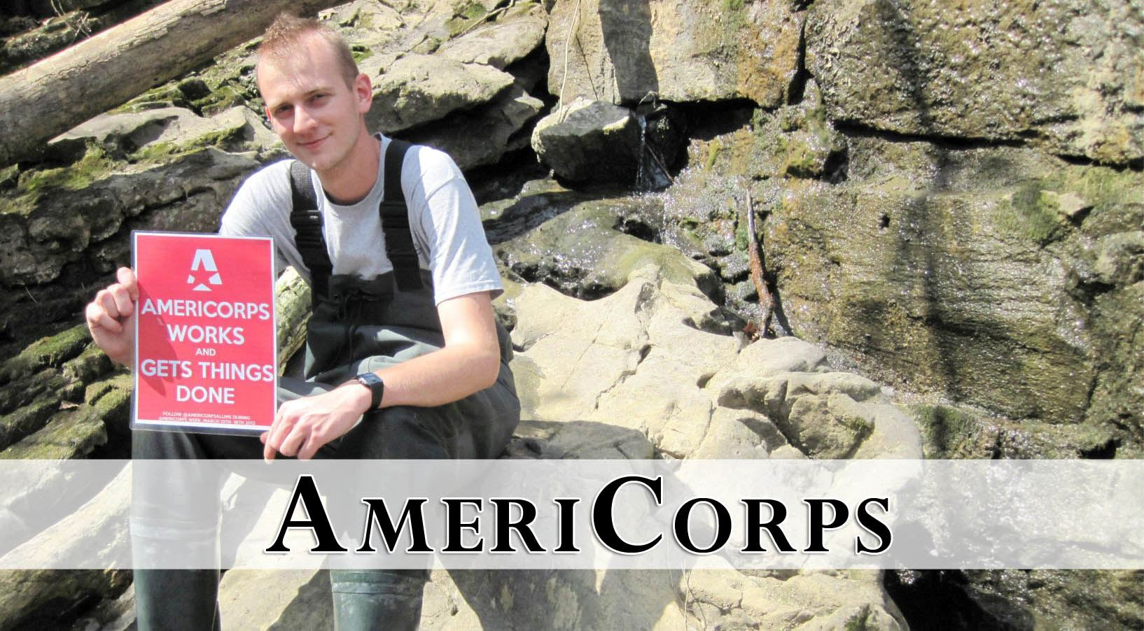 "young man sitting on rocks holding ""americorps get things done"" sign"